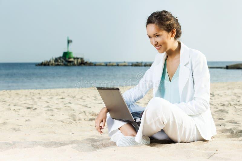 Bizneswoman z laptopu obsiadaniem na plaży obrazy royalty free