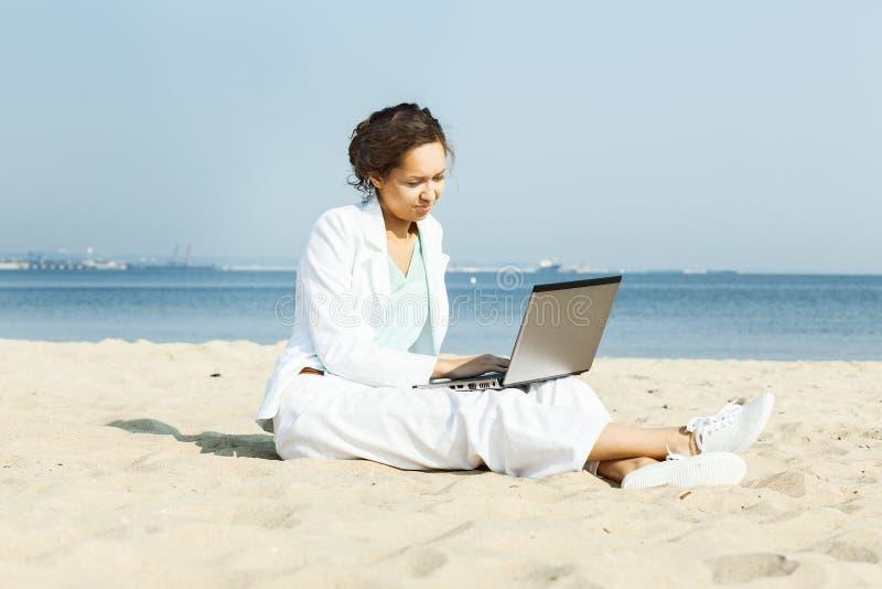 Bizneswoman z laptopu obsiadaniem na plaży obraz stock