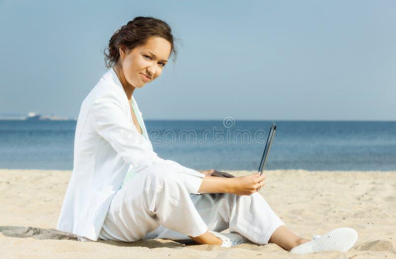 Bizneswoman z laptopu obsiadaniem na plaży zdjęcia stock