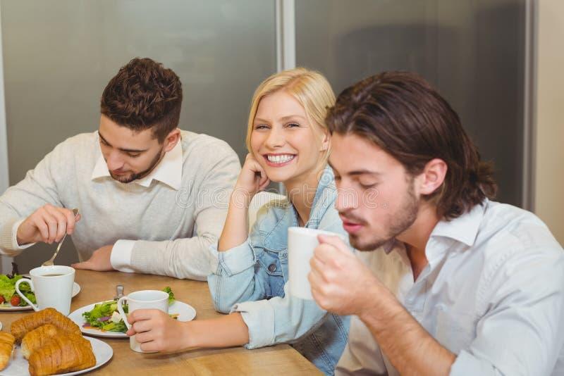 Bizneswoman z męskimi kolegami ma przekąski i kawę w bakłaszce obraz royalty free