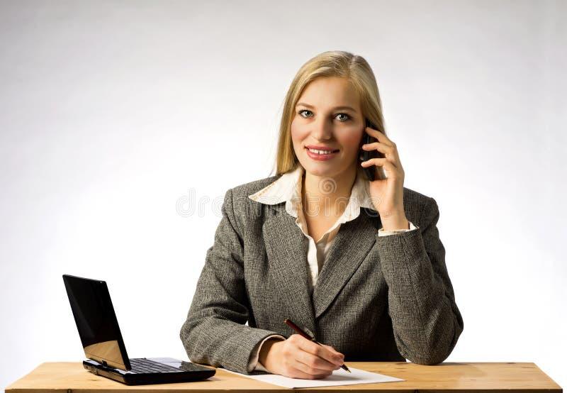 Bizneswoman z szarym kurtki obsiadaniem przy biurowym tesk opowiada na telefonie i pisze notatce z piórem na papierze, zdjęcie royalty free