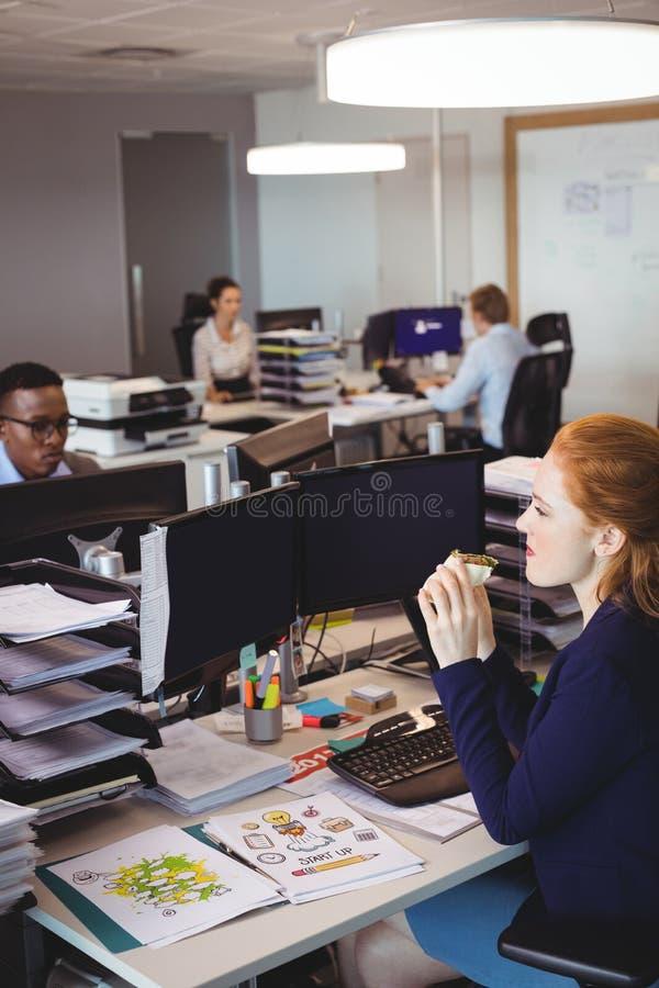Bizneswomanu łasowania przekąska podczas gdy koledzy pracuje w kreatywnie biurze zdjęcie royalty free