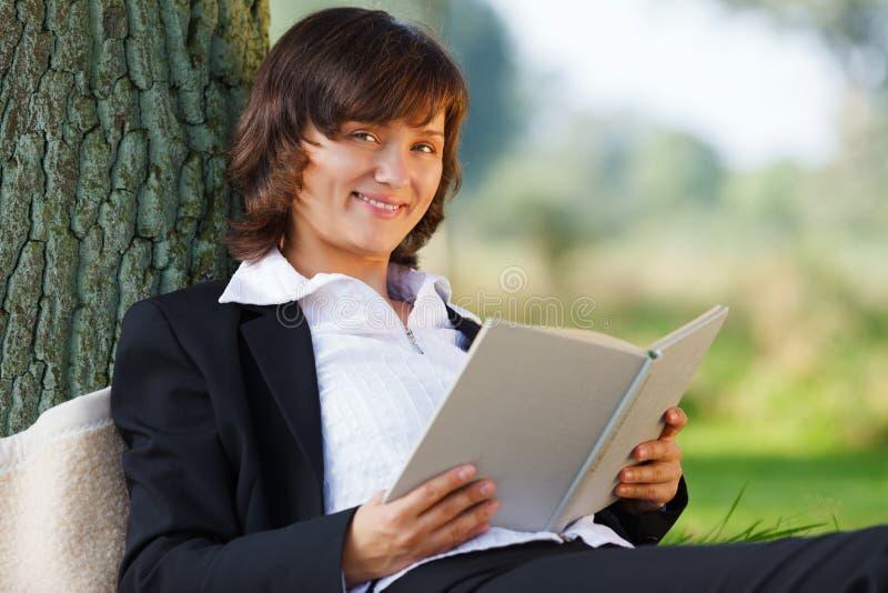 Bizneswomanu czytać plenerowy w parku zdjęcia royalty free