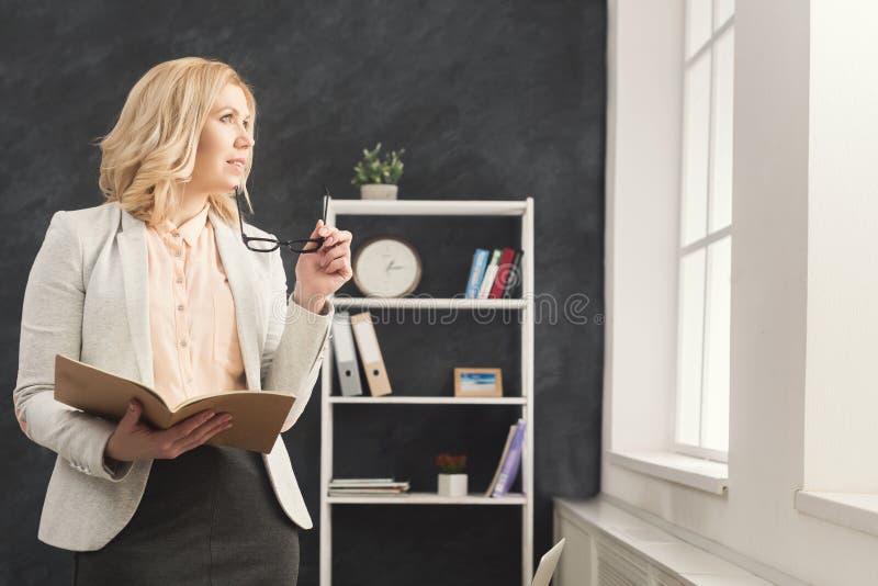 Bizneswomanu czytania dokument przy biurem zdjęcia stock