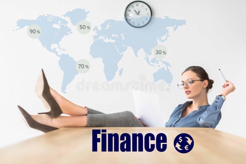 Bizneswomanu czytania obsiadanie z nogami na stole z finansową inskrypcją i dokumenty zdjęcie stock
