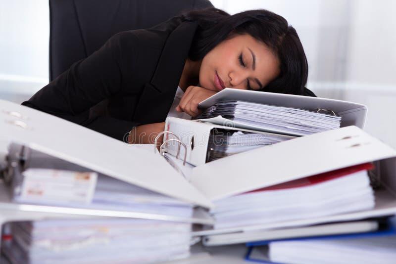 Bizneswomanu dosypianie na stosach falcówki obraz stock