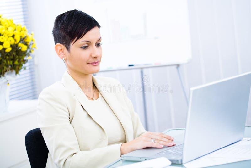 bizneswomanu działanie laptopa zdjęcie stock