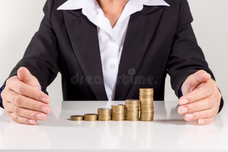 Bizneswomanu kładzenia moneta Na stercie Złote monety fotografia royalty free