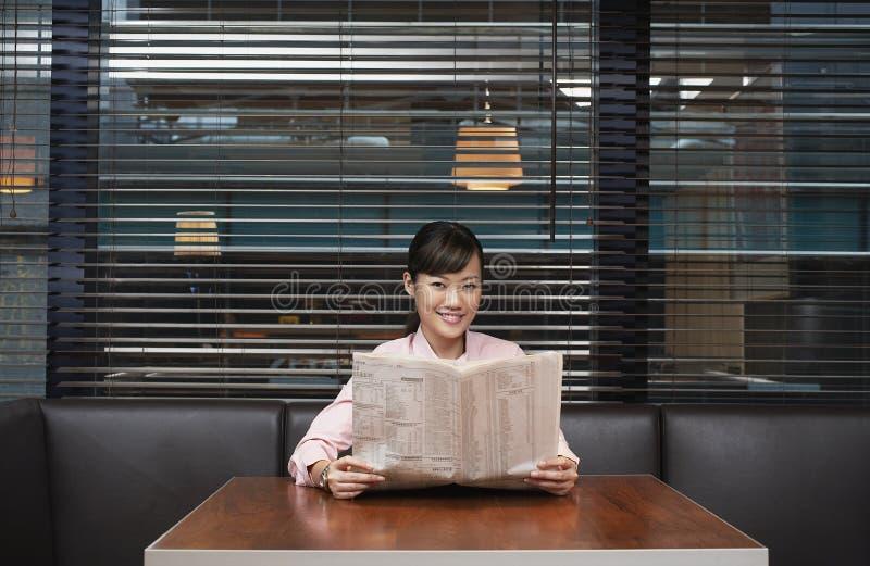 Bizneswomanu mienia gazeta Przy kawiarnia stołem zdjęcia stock