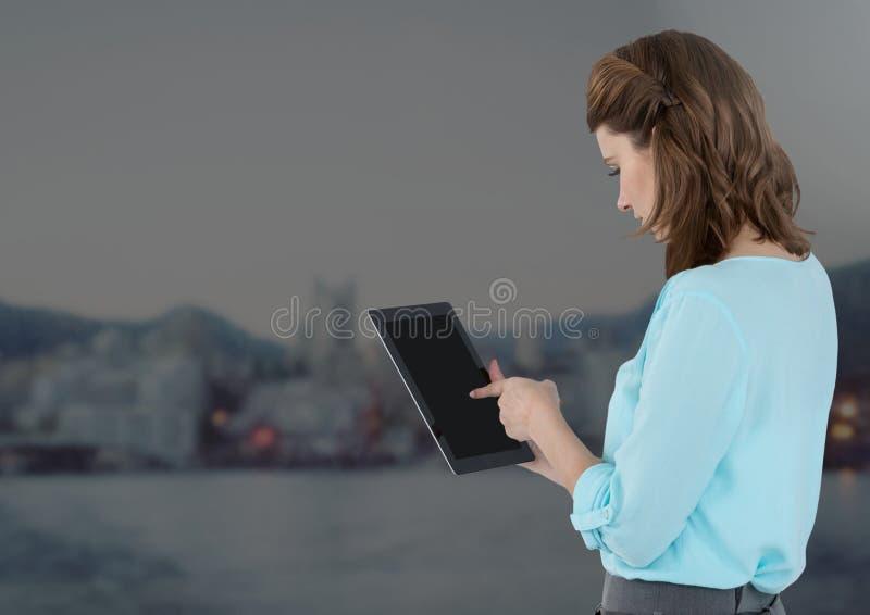 Bizneswomanu mienia pastylka z odległym popielatym miasta tłem zdjęcie stock