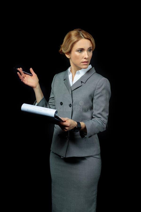 Bizneswomanu mienia schowek z dokumentami i gestykulować z piórem obrazy stock