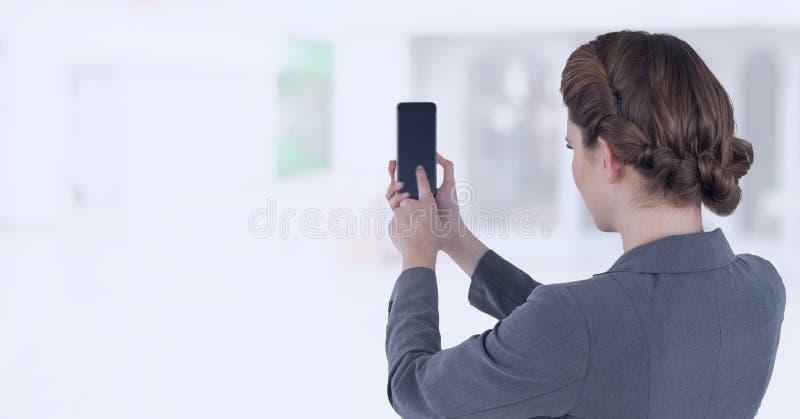 Bizneswomanu mienia telefon komórkowy w jaskrawym zakupy centrum handlowym zdjęcie royalty free