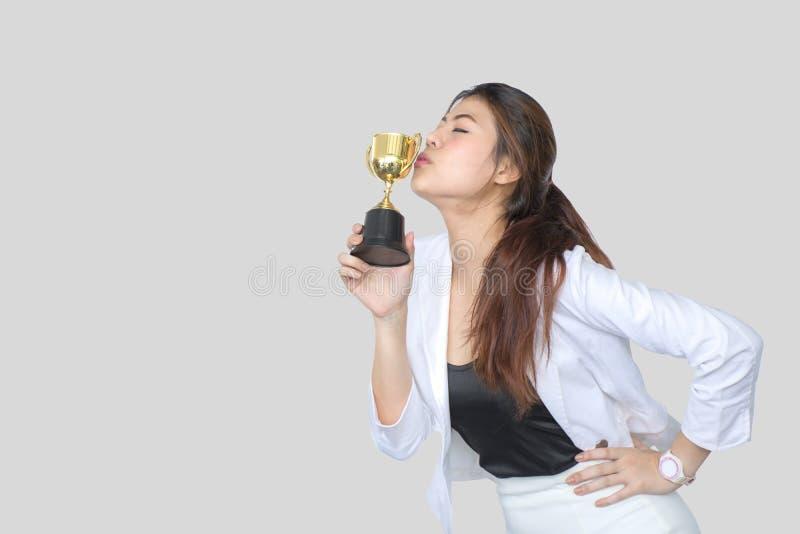Bizneswomanu mienia trofeum nagroda dla sukcesu w biznesie, odizolowywająca na szarym tle obrazy royalty free