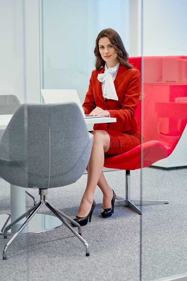 Bizneswomanu obsiadanie na czerwonym krześle w szklanym biurze i pracach zdjęcia stock