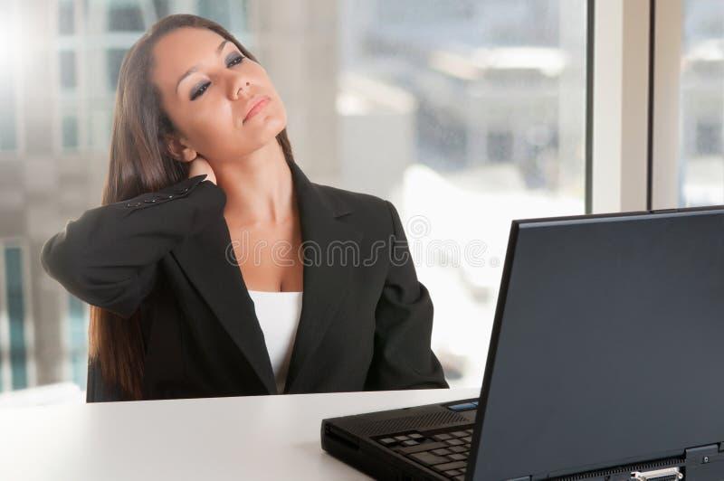 Bizneswomanu obsiadanie przy Jej biurkiem Męczącym zdjęcie stock