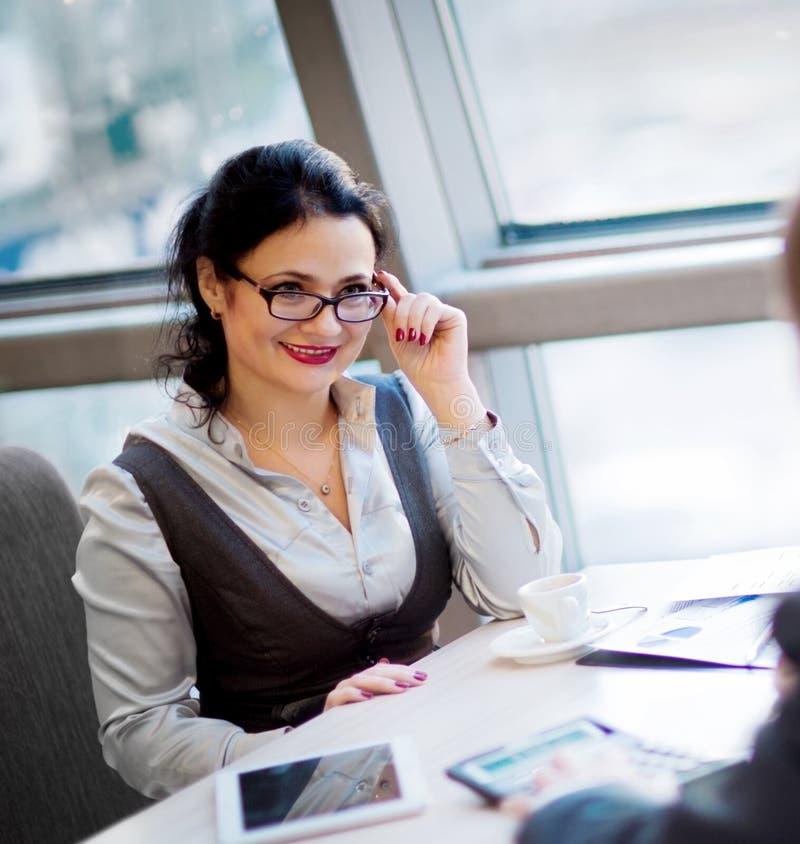 Bizneswomanu obsiadanie przy miejsca pracy i czytania papierem obraz stock