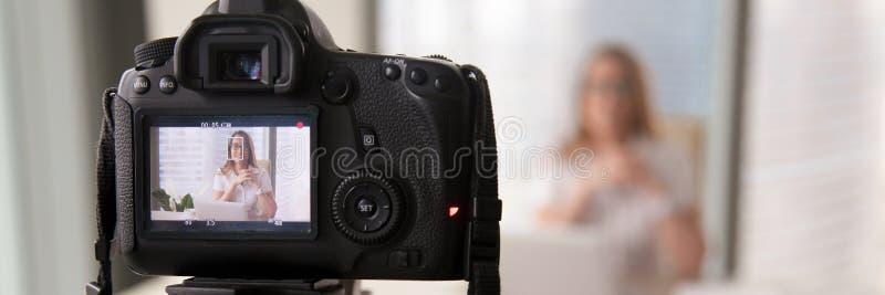 Bizneswomanu obsiadanie przy nowożytnym biurem opowiada na kamery magnetofonowej prezentacji zdjęcie stock