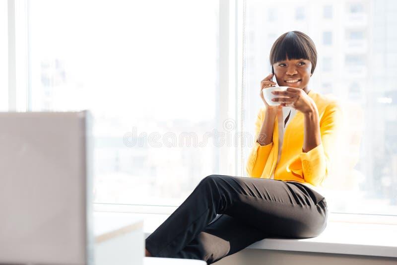 Bizneswomanu pić kawowy i opowiadać na telefonie fotografia stock