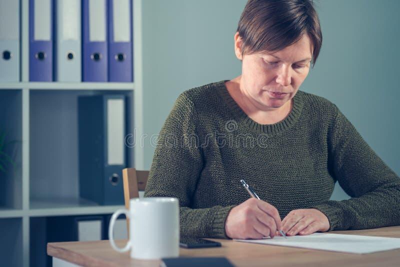 Bizneswomanu podpisywania papiery lub writing notatki zdjęcia royalty free