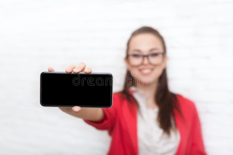 Bizneswomanu przedstawienia komórki telefonu mądrze ekran z pustych kopii przestrzeni odzieży kurtki czerwonych szkieł szczęśliwy zdjęcie stock