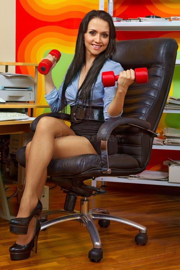Bizneswomanu rozciąganie z dumbbells