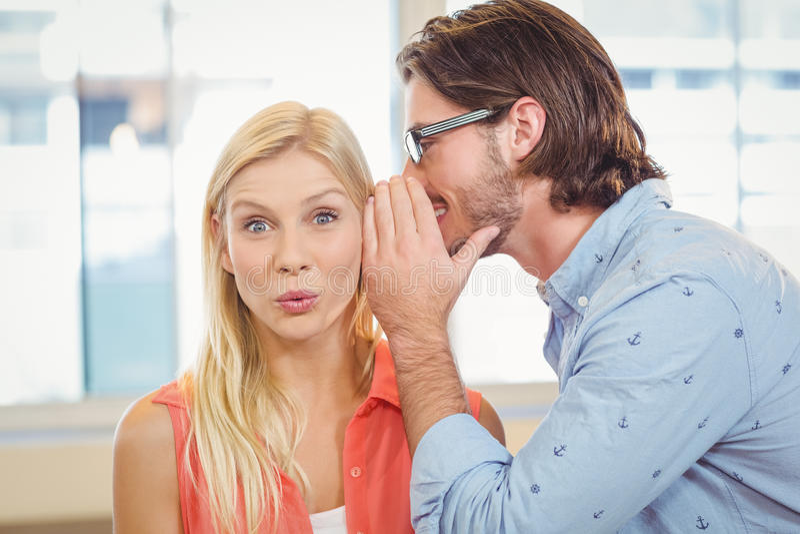 Bizneswomanu słuchanie plotkować który męski kolega szepcze obraz stock