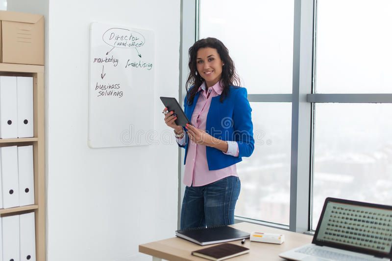 Bizneswomanu writing dnia plan na białej desce, nowożytny biuro Boczny widok caucasian żeński pracownika planowania rozkład zdjęcie stock