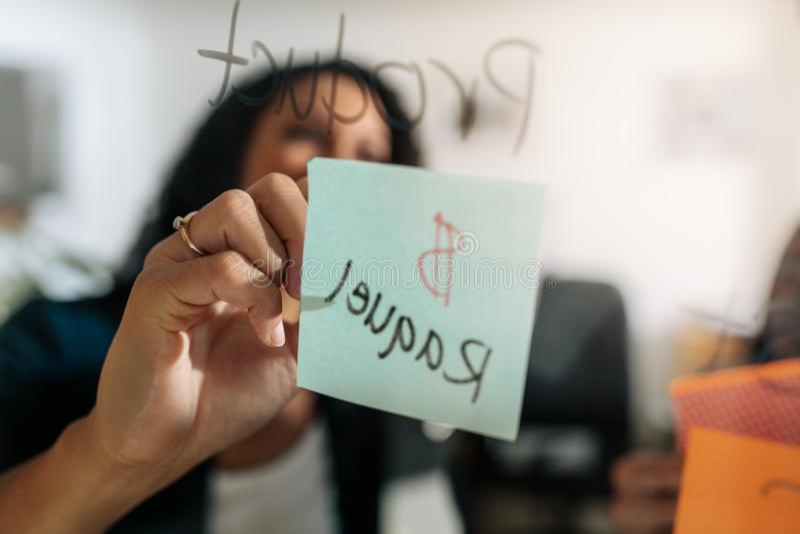 Bizneswomanu writing na kleistej notatce klajstrującej na szklanej desce ja zdjęcia royalty free