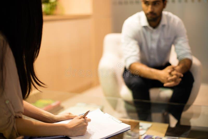 Bizneswomanu writing na schowku podczas gdy dyskutujący z męskim kolegą obraz stock