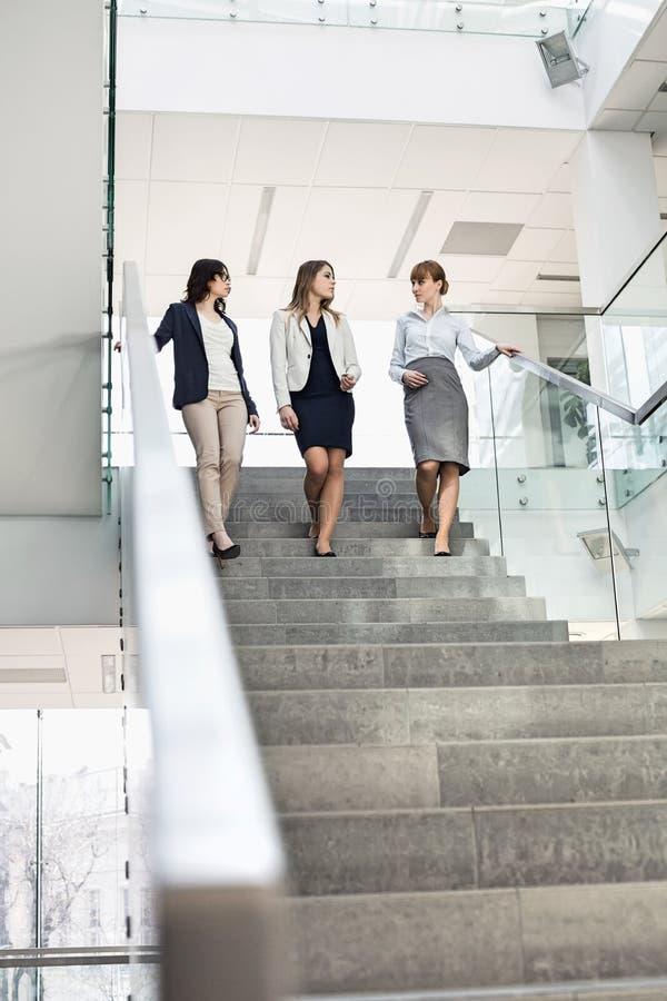 Bizneswomany conversing podczas gdy ruszający się w dół kroki w biurze obraz royalty free
