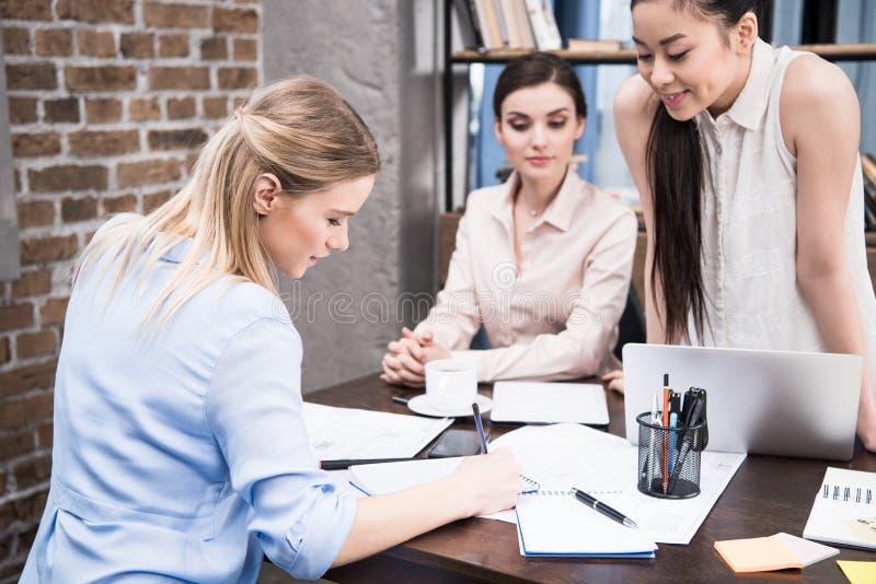 Bizneswomany dyskutuje projekt i pisze coś w notepad przy workspace fotografia stock