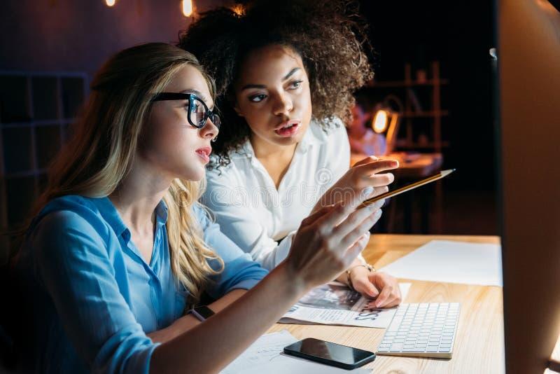 Bizneswomany pracuje na komputerze podczas gdy dyskutujący nowego projekt obrazy stock