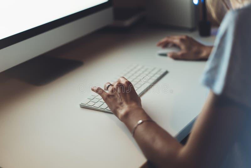 Bizneswomany pracuje przy biurem z monitoru komputerem, młody modnisia kierownik pisać na maszynie na klawiaturze, zbliżenie palc obrazy royalty free