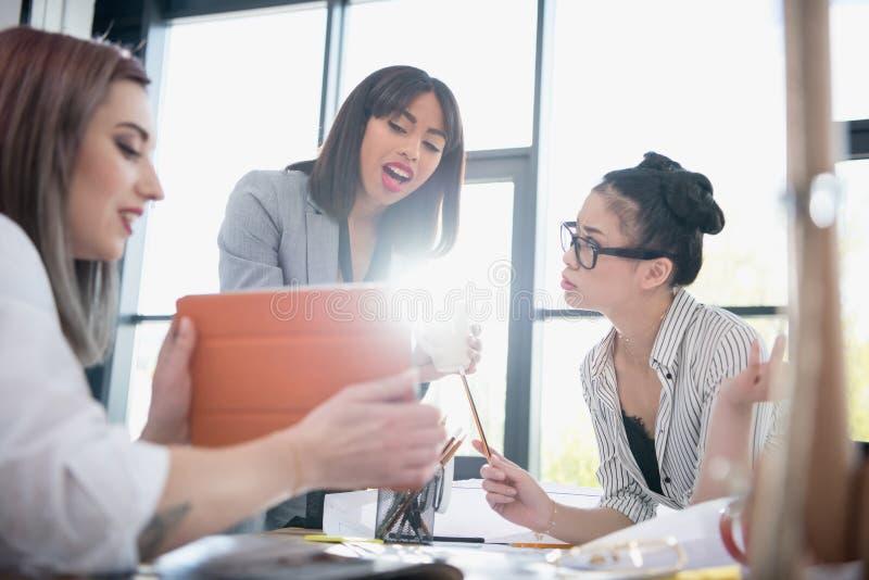 Bizneswomany pracuje wpólnie i używa cyfrową pastylkę w biurze obraz royalty free