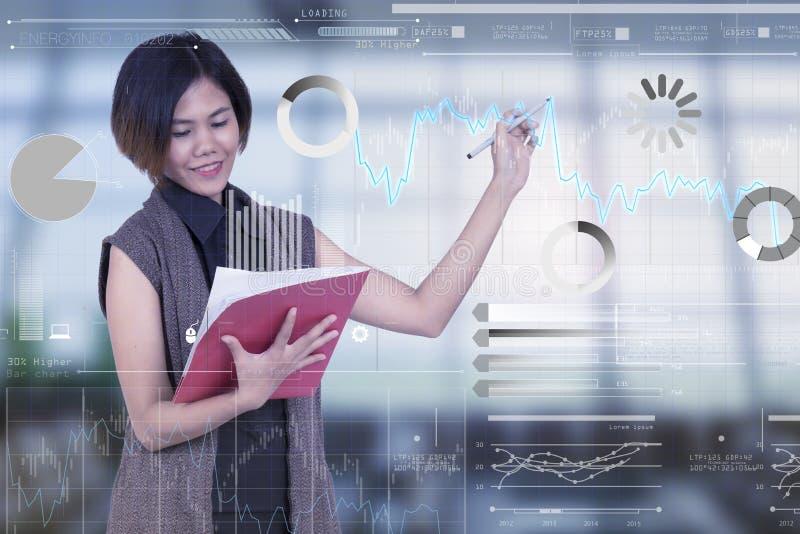 Bizneswomany trzyma dokument i pisze wykresie cyfrowym fotografia stock