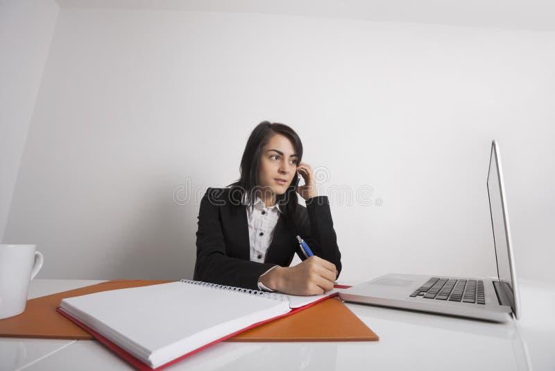 Bizneswomany używa telefon komórkowego przy biurowym biurkiem podczas gdy pisać notatkach od laptopu obraz stock