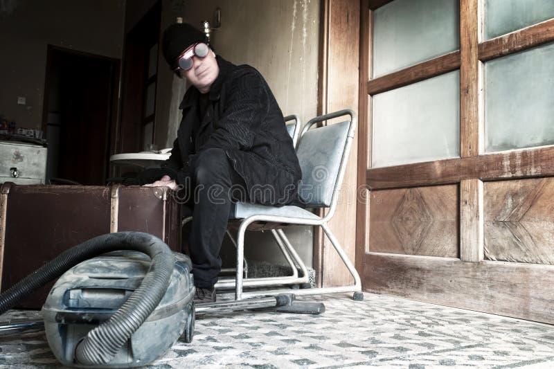 Bizzare-Mann, der auf einem Stuhl sitzt stockfotos
