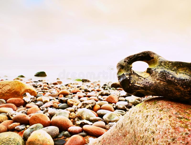 Bizzare rock on the pebbles beach, dramatic sky above. Stony offshore. stock images
