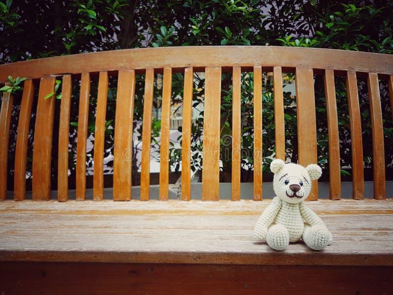 björn för amigurumivirkningnalle på den ensamma bänken royaltyfria foton
