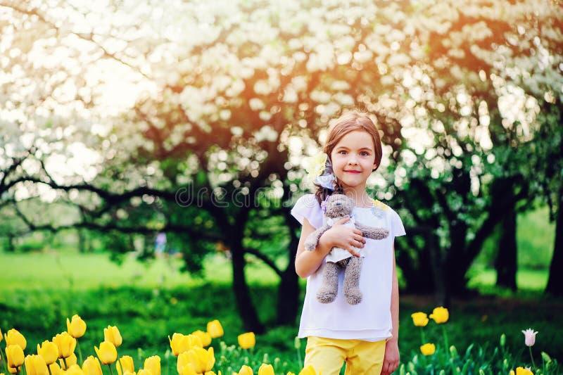 Björnen för nallen för den gulliga lyckliga barnflickan går den hållande på våren med gula tulpan på bakgrund royaltyfria foton