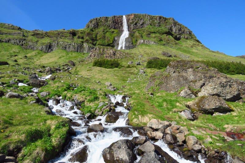 Bjarnarfoss vattenfall och flod som kör till och med gröna fält i sommar, Budir, Snæfellsnes, Island royaltyfria foton