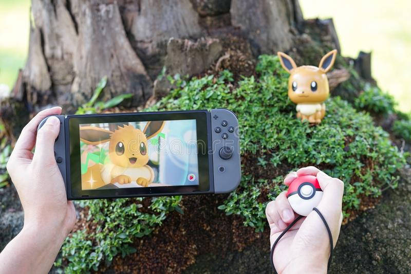 Nintendo Switch and Pokemon Let`s Go Eevee. BKK - Nov 17, 2018 : A photo of Pokemon Let`s go on Nintendo Switch. 2 special editions launched on Nov 16, 2018 stock photo