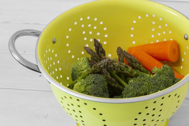 Bläckfiskar, broccoli- och morotsgrönsaker i genomskinliga grönfärgade halsar arkivbild