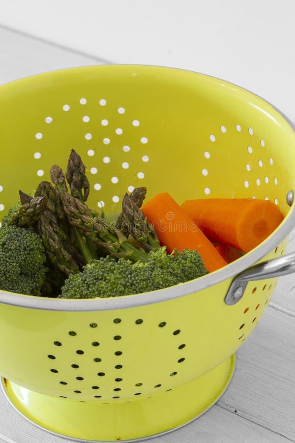 Bläckfiskar, broccoli- och morotsgrönsaker i genomskinliga grönfärgade halsar royaltyfria foton
