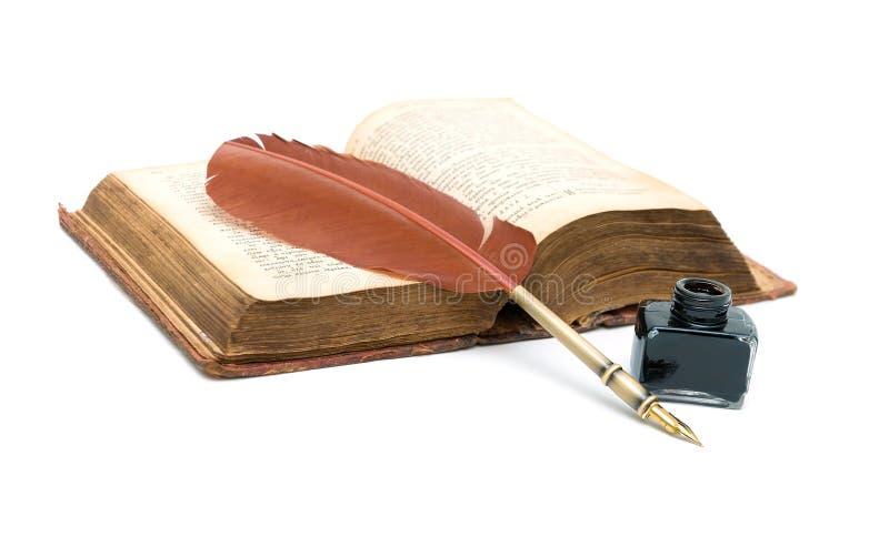 Bläckhornen, pennan och ett gammalt öppnar boken på vit bakgrund arkivbilder