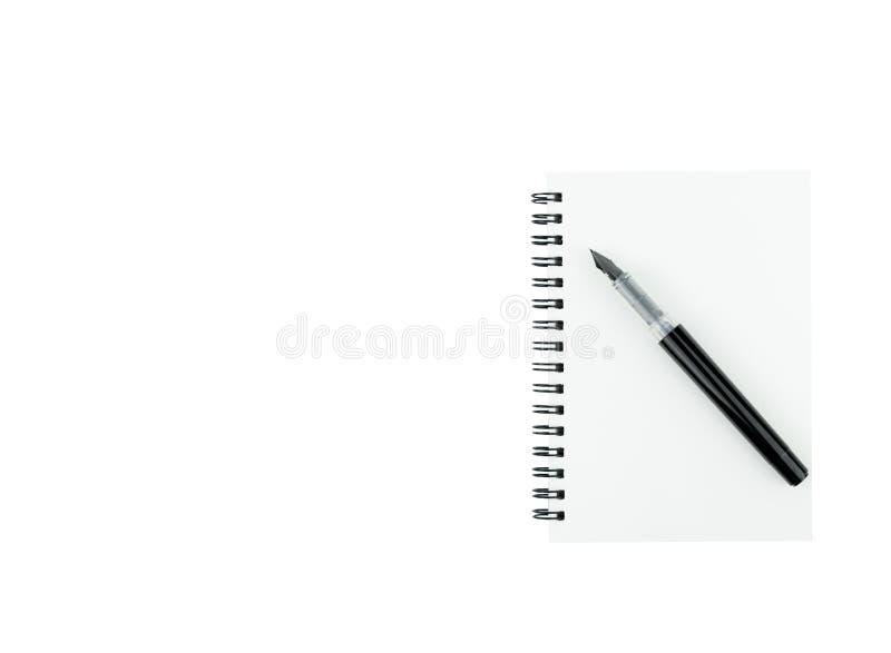 Bläckpenna på anmärkningsboken med kopieringsutrymme på isolerad vit bakgrund royaltyfria foton