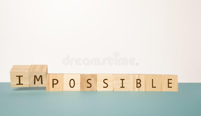 Bläddra träkub två för att ändra det omöjliga ordet till möjligheten på neutral bakgrund royaltyfri foto