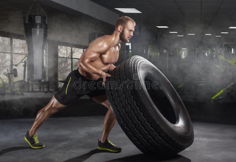 Bläddrande och rullande gummihjul för ung vuxen man under övning i idrottshallen royaltyfri foto
