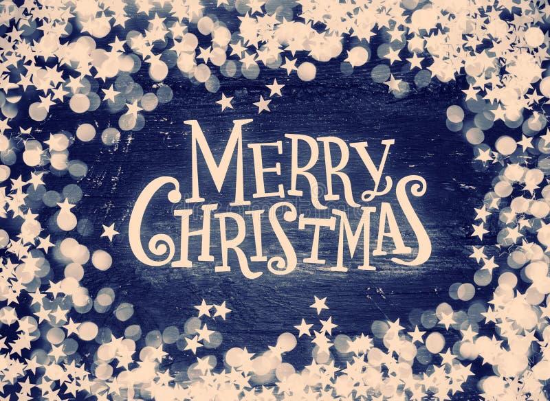 Blänka stjärnor, och defocused ljus på grungeträ med glad jul smsar Tonat Retro arkivfoto