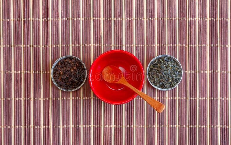 Blätter des grünen Tees und des schwarzen Tees in den kleinen Untertassen und in einem leeren roten Veilchen mit einem hölzernen  lizenzfreies stockbild